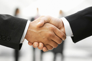 Image of a close-up handshake between two businessmen