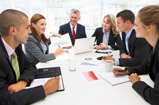 Image of a group of business people meeting around a large white conference table