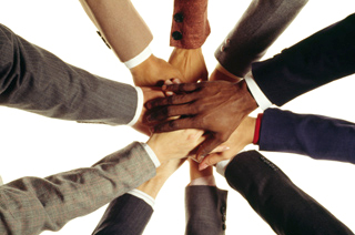 Image of a bunch of business mens hands coming together in a huddle