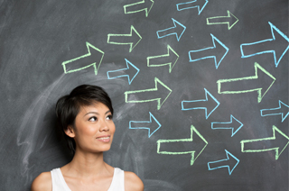 Image of a woman leaning against a chalkboard while looking to the right and at arrows draw on the chalkboard