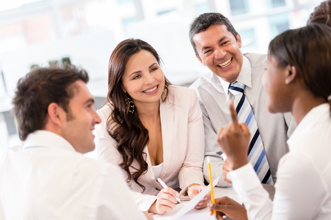Image of a group of smiling business people at a meeting