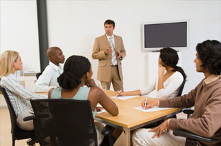Image of a man in business suit speaking to group of individuals seated at table