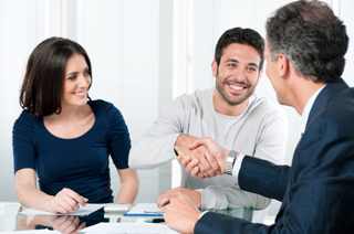 Image of a meeting with two men shaking hands while a woman looks at them