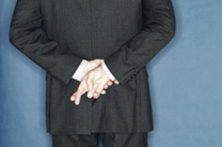 Image of a man in business suit with fingers crossed behind his back