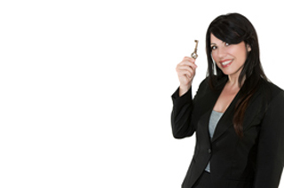 Image of a business woman holding a key up in her right hand