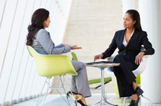 Image of two business women seated at a table having a discussion